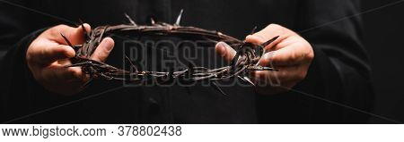 Horizontal Crop Of Priest Holding Wreath With Spikes Isolated On Black
