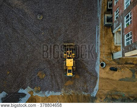 Above view of tractor doing earthwork in spring. Above view