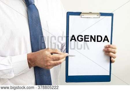 Businessman With Agenda Word. Businessman Holding Paper With Agenda Word