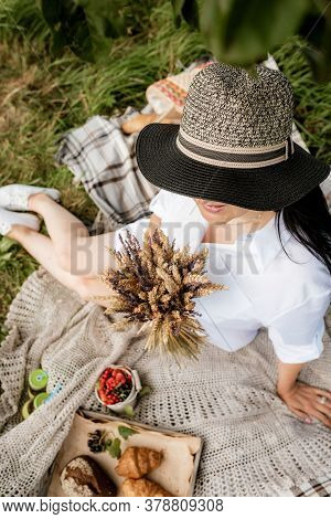 Little Beautiful Girl Hid In A Big Straw Hat And Rests On A Picnic In Fields. Summer Time.bouquet Of