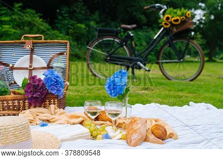 Summer Picnic On Sunny Day With Bread, Fruit, Bouquet Hydrangea Flowers, Glasses Wine, Hat, Book. Pi