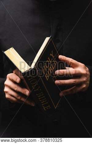 Partial View Of Pastor Reading Holy Bible Isolated On Black