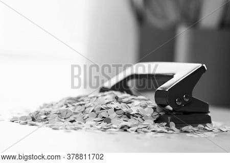 Black and white photo of hole punch and paper bits