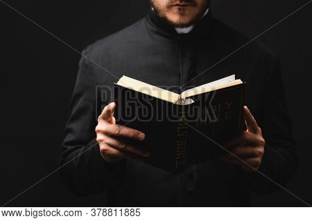 Partial View Of Bearded Pastor Reading Holy Bible Isolated On Black