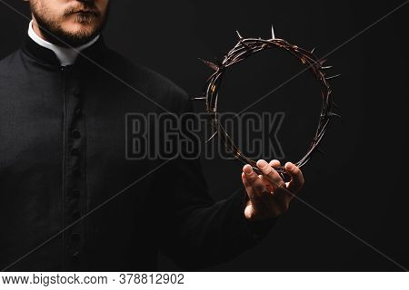 Cropped View Of Pastor Holding Wreath With Spikes In Hand Isolated On Black