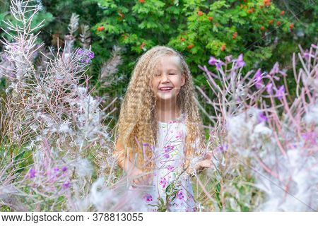 A Little Blonde Girl In A White Sundress Stands Surrounded By Blooming Sally, Fireweed. Summer, Natu