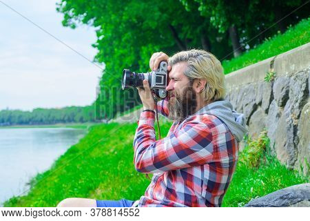 Handsome Man Traveler Making Photos Near River. Travel And Tourism. Male Photographer With Camera. H