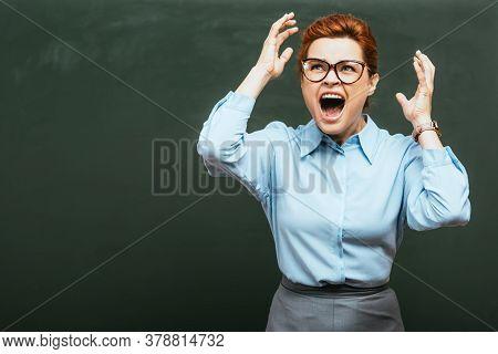 Irritated Teacher Gesturing And Screaming Near Chalkboard