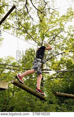 Young Guy Runs An Obstacle Course From Tree To Tree On A Rope Park