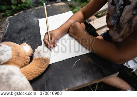Partial View Of African American Child Holding Pencil While Writing On Paper
