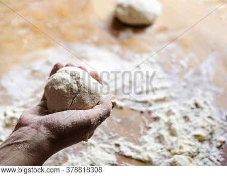 A Female Hand Holds A Flour Dough With A Wooden Board Dirty With Flour In The Background. Kneading A