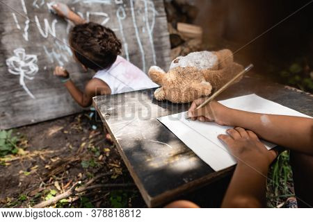 Partial View Of African American Child Writing Near Kid And Chalkboard