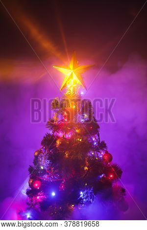 Christmas tree with shining star and frozen mist