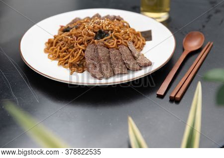 Korean Black Bean Sauce, Jajjangmyeon Noodles With Sliced Beef On Top With Wooden Spoon And Chopstic