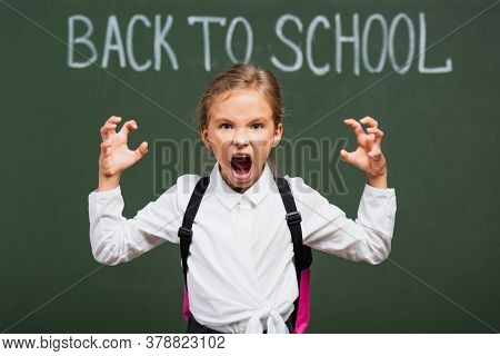 Selective Focus Of Angry Schoolgirl Showing Scaring Gesture Near Chalkboard With Back To School Lett