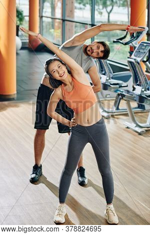 Smilng Young Multi-ethnic Couple Doing Side Bends And Looking At Camera