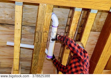 Pvc Plastic Sewer Toilet White Pipe In The Plumber Gluing, On Wooden Frame Ceiling Beam Of House Sof