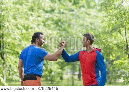 Two Men After Workout Outdoor Shake Hands. Active And Healthy Lifestyle Concept.