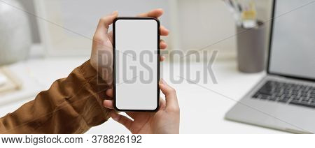 Hands Holding Smartphone With Clipping Path At Worktable In Home Office Room