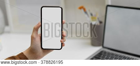 Female Hand Holding Smartphone With Clipping Path At Worktable  In Home Office Room