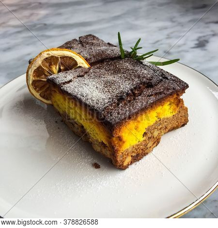 Lemon Brownies With Dried Lemon Sliced On A White Ceramic Plate.