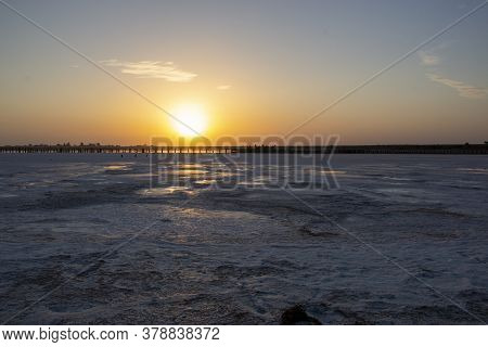 Sunrise Over The Pink Lake And Salt Shores, The Reflection Of The Suns Rays On The Mirror Surface Of
