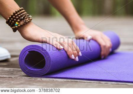 Girl Unwinding Gymnastic Mat For Yoga Class Outdoors, Close-up