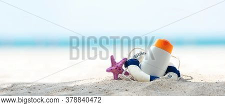 Protective Sunscreen Or Sunblock And Sunbath Lotion In White Plastic Bottles With Sandals On Tropica
