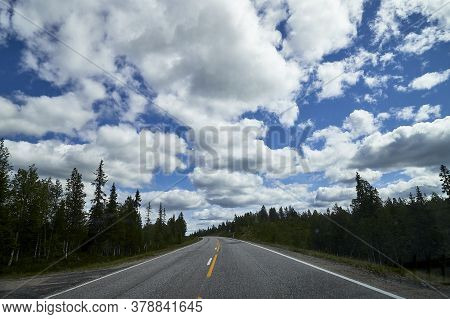 Beautiful Landscape With Blue Sky, White Clouds And The Road That Goes To The Horizon With The Fores