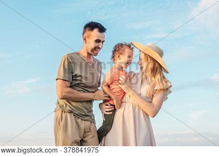 Young Happy Family With Little Boy Play Together On Nature. Mother And Father Tickle His Son And Lau