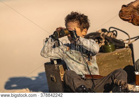 Post Apocalyptic Hero Boy With Binoculars Outdoors. Desert And Dead Wasteland On The Background. Her