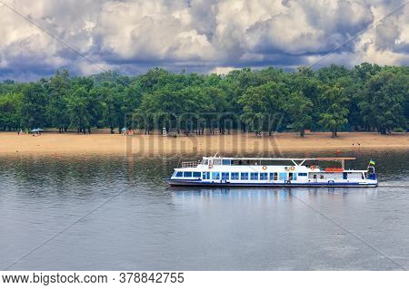 A River Tram With A Few Tourists Resting Goes Along The River Against The Backdrop Of Coastal Greene