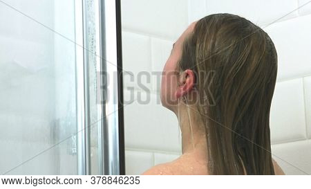 Woman under shower. She is washing hair and body in splashing water. Healthy and pure hair. Cosmetic treatments for the body, beauty care. Back view of naked woman enjoying shower.