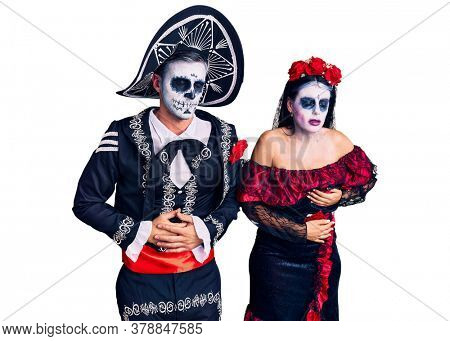 Young couple wearing mexican day of the dead costume over background with hand on stomach because indigestion, painful illness feeling unwell. ache concept.