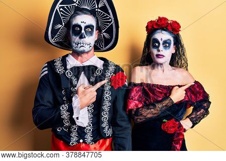 Young couple wearing mexican day of the dead costume over yellow pointing aside worried and nervous with forefinger, concerned and surprised expression