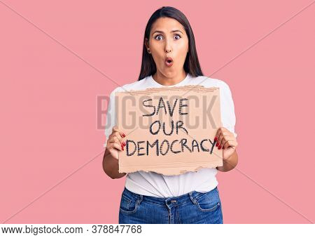 Young beautiful woman holding save our democracy cardboard banner scared and amazed with open mouth for surprise, disbelief face