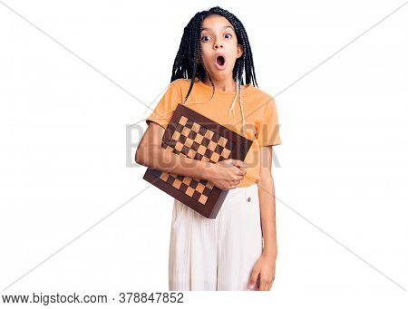 Cute african american girl holding chess scared and amazed with open mouth for surprise, disbelief face