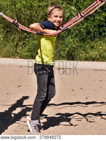A Seven-year-old Boy On The Outdoor Playground
