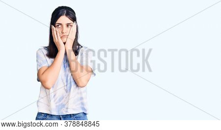Young beautiful girl wearing casual t shirt tired hands covering face, depression and sadness, upset and irritated for problem