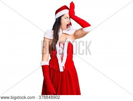Young beautiful caucasian woman wearing santa claus costume surprised with hand on head for mistake, remember error. forgot, bad memory concept.