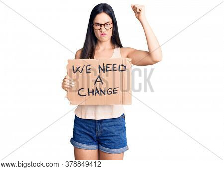 Young beautiful caucasian woman holding we need a change banner annoyed and frustrated shouting with anger, yelling crazy with anger and hand raised