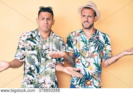 Young gay couple of two men wearing summer hat and hawaiian shirt clueless and confused with open arms, no idea concept.