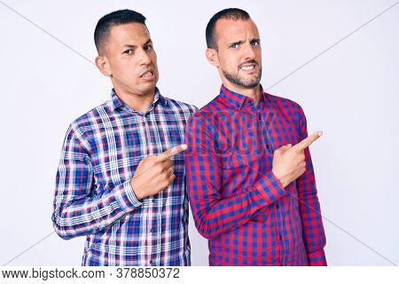 Young gay couple of two men wearing casual clothes pointing aside worried and nervous with both hands, concerned and surprised expression