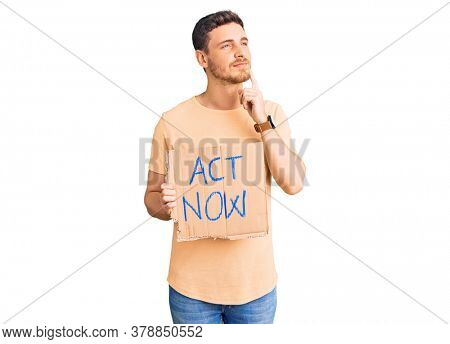 Handsome young man with bear holding act now banner serious face thinking about question with hand on chin, thoughtful about confusing idea