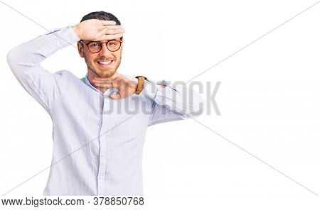 Handsome young man with bear wearing elegant business shirt and glasses smiling cheerful playing peek a boo with hands showing face. surprised and exited