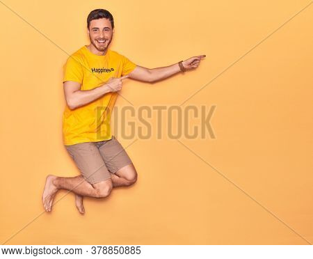 Young handsome hispanic man wearing t shirt with happiness word message smiling happy. Jumping with smile on face over isolated yellow background