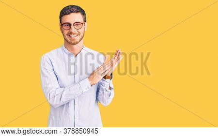 Handsome young man with bear wearing elegant business shirt and glasses clapping and applauding happy and joyful, smiling proud hands together