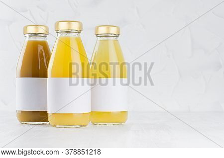 Orange, Yellow Fruit Juices Set In Glass Bottles With Cap, White Blank Labels Mock Up Group On White