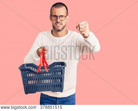 Young handsome man holding supermarket shopping basket annoyed and frustrated shouting with anger, yelling crazy with anger and hand raised