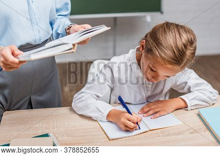Partial View Of Teacher With Book Near Schoolgirl Sitting At Desk And Writing In Copy Book
